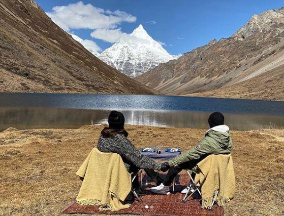 أنوشكا وفيرات يجلسان أمام الجبال