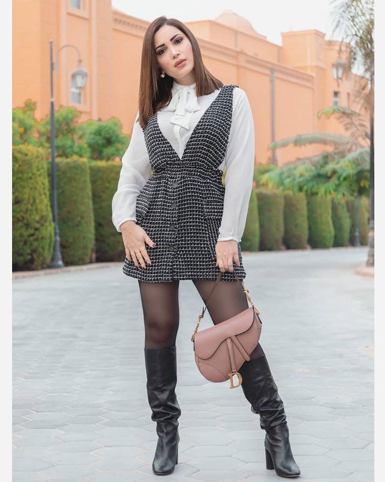 نسقت نسرين طافش جزمة باللون الأسود مع فستان قصير