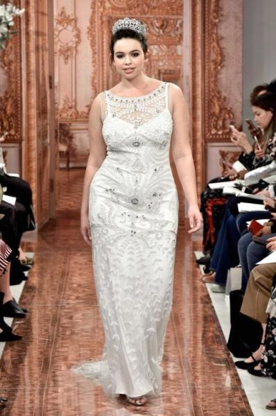 89875a34a أمام التصميم الثاني فجاء بـ أكمام طويلة شفّافة ومطرزة بالورود البيضاء،  ليخفي امتلاء الذراع أيضًا، مع تنورة تول واسعة. فساتين زفاف ثيا Theia