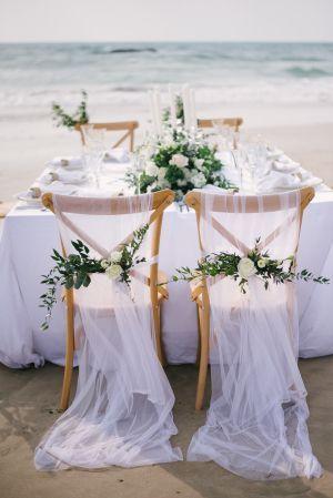 كرسي زفاف مزين بالتول الأبيض والأزهار