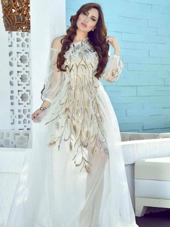 8f6898a7c نادين نجيم اختارت فستان سهرة محتشمًا باللون الأبيض، تصميمه راقٍ جدًّا مع  أكمام طويلة وقصة منسدلة، ياقته على شكل حرف V لكن غير مبالغ بها، ولونه  الأبيض بدا ...