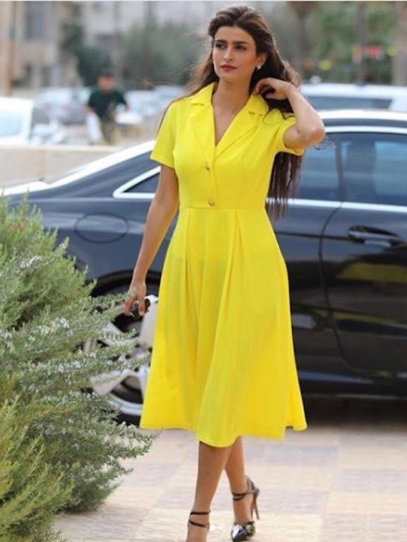 علا الفارس مشرقية في فستان أصفر مستوحًى من الخمسينيات