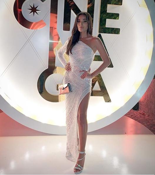 فستان بقصة الكتف الواحد باللون الأبيض اعتمدته نادين نجيم