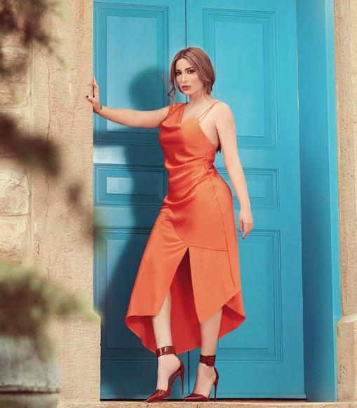 فستان ميدي باللون البرتقالي اعتمدته نسرين طافش