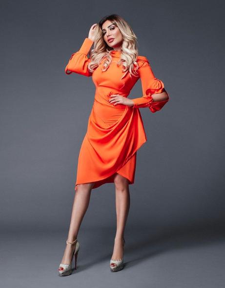 فستان قصير باللون البرتقالي اختارته أمل العوضي