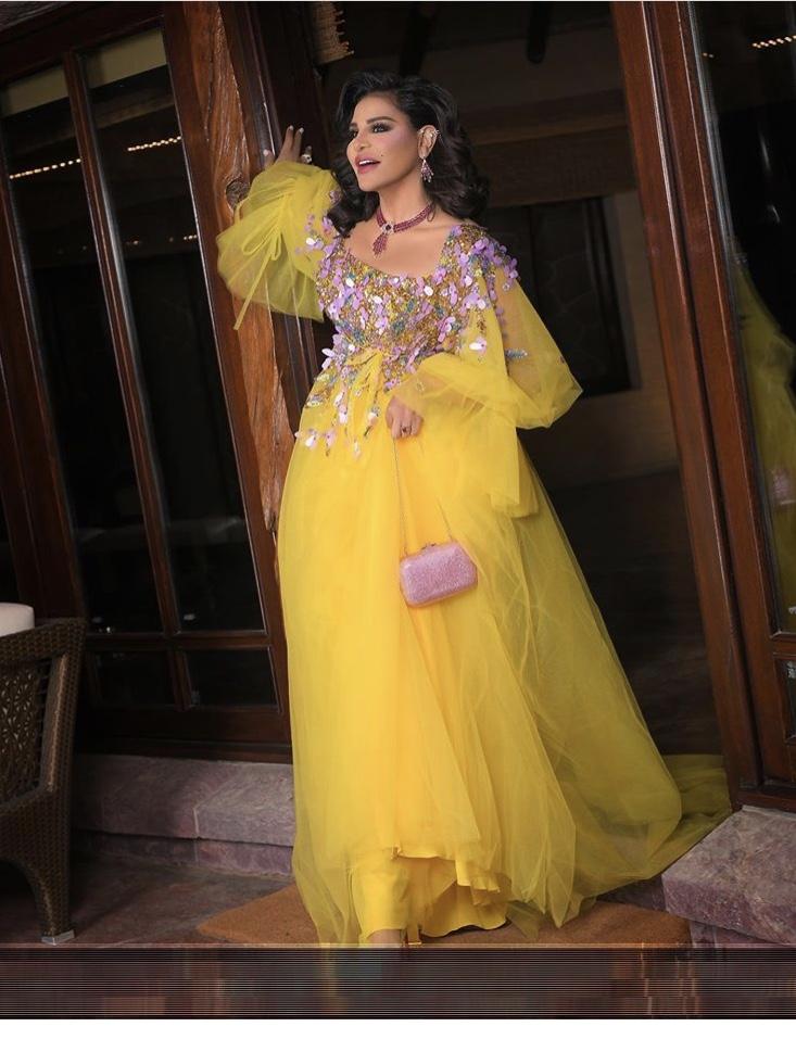 أحلام بفستان أصفر فاقع مع الأكمام المنفوشة من التول
