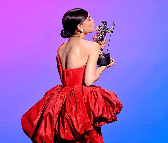 Sofia Carson بفستان أحمر أنثوي بكتف واحد