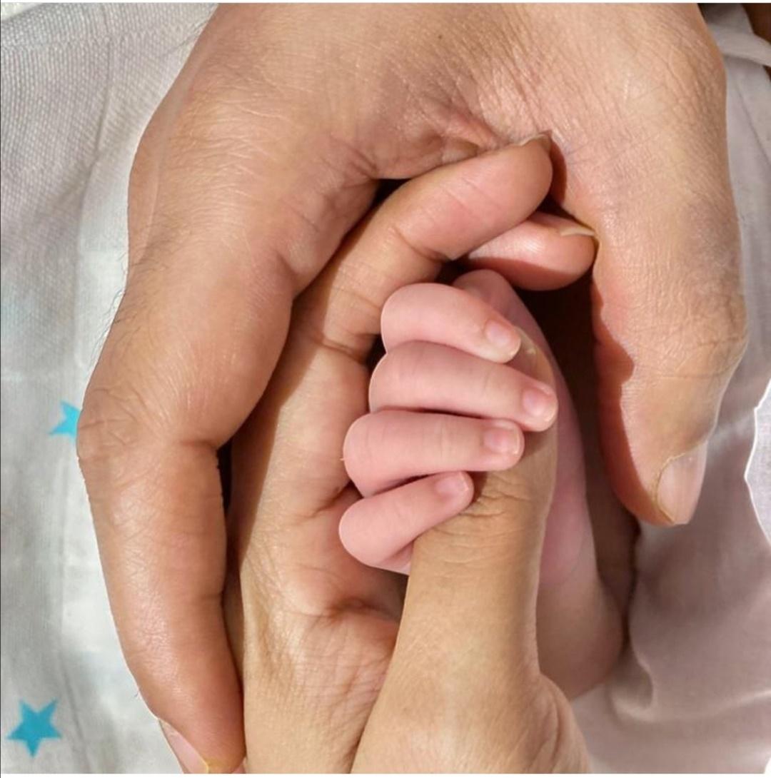نيتي موهان وزوجها نيهار بانديا يحملان ابنهما أريافير- الصورة من حساب نيتي موهان على إنستغرام