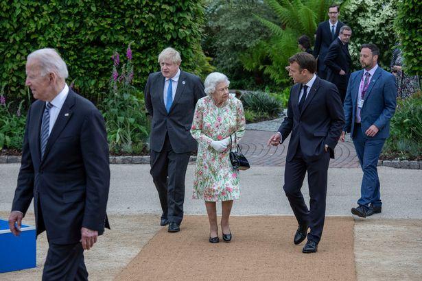 الملكة إليزابيث تتوسط بوريس جونسون والرئيس الفرنسي إيمانويل ماكرون- الصورة من موقع ميرور