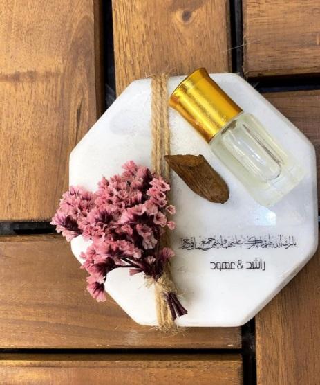 توزيعات أعراس من الرخام المُزين بزجاجات العطر والورود