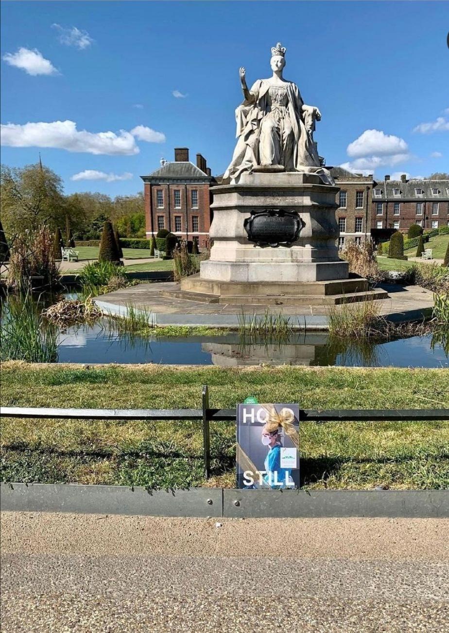 نسخة الكتاب في مواجهة السور المنخفض حول البركة حيث يلوح تمثال الملكة فيكتوريا التذكاري- الصورة من حساب دوق ودوقة كامبريدج على إنستغرام.jpg
