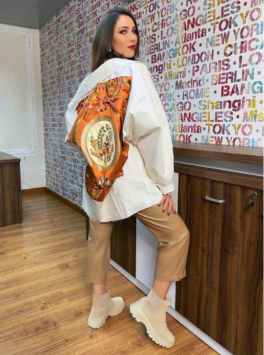 دانييلا ترتدي سترة بيضاء واسعة مزدانة بالرسوم الملونة من الوراء مع سروال جلدي خردلي اللون. من حساب النجمة على انستغرام.