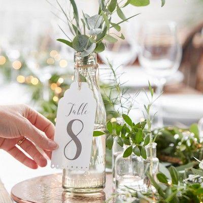 ترقيم الطاولات في حفل الزفاف باستخدام زجاجات مملوءة بفروع الأشجار